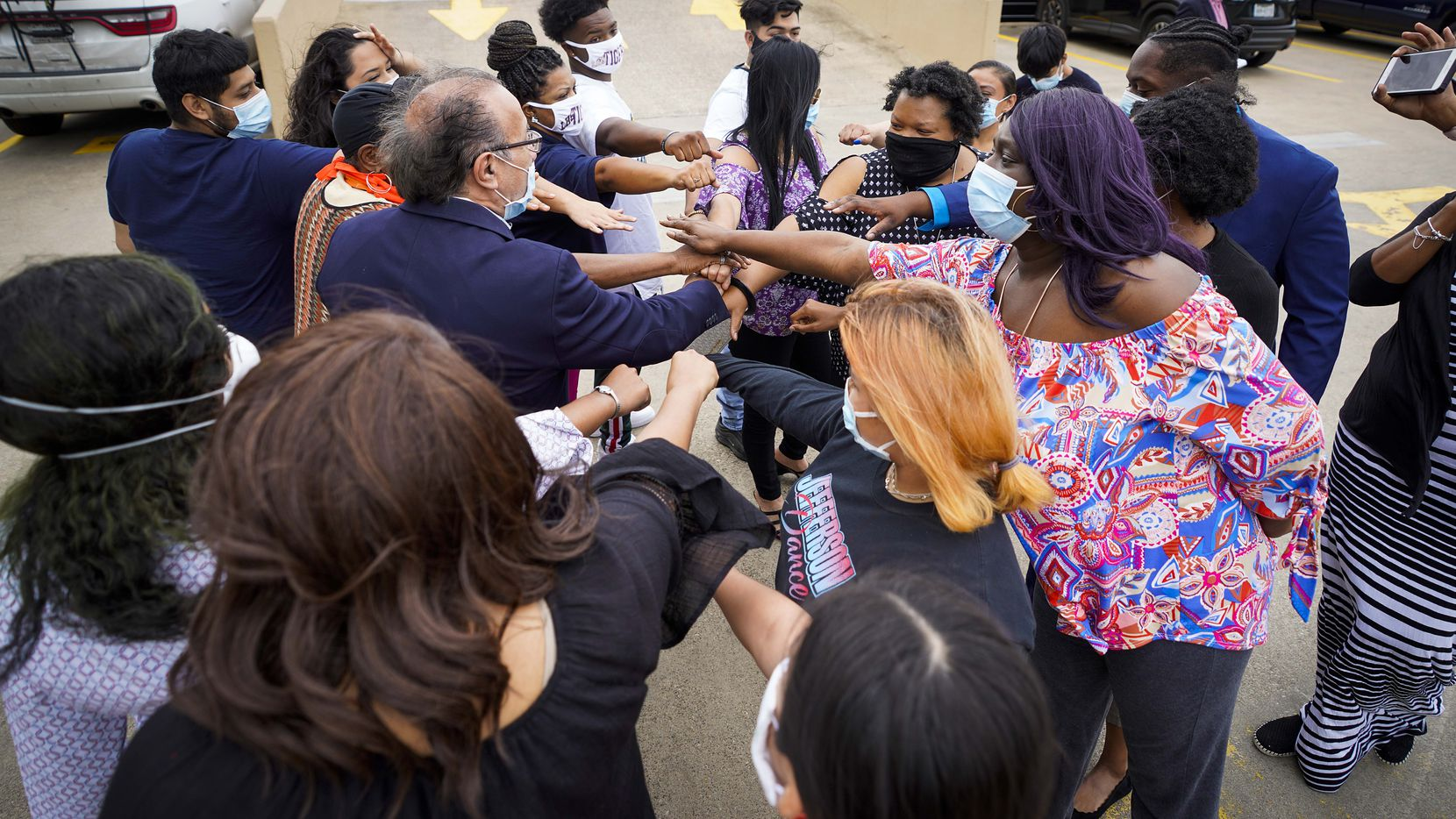 Students, parents and community organizers gather around activist Carlos Quintanilla as they huddle before addressing media outside the Dallas ISD administration building on Tuesday, May 12, 2020, in Dallas.  The protesters want DISD to backtrack on virtual graduations and hold in-person events instead.