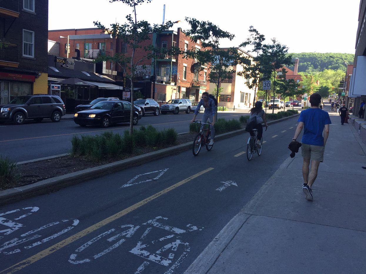 Bicyclists use a protected bike lane in Montreal on June 13, 2017, in Montreal.