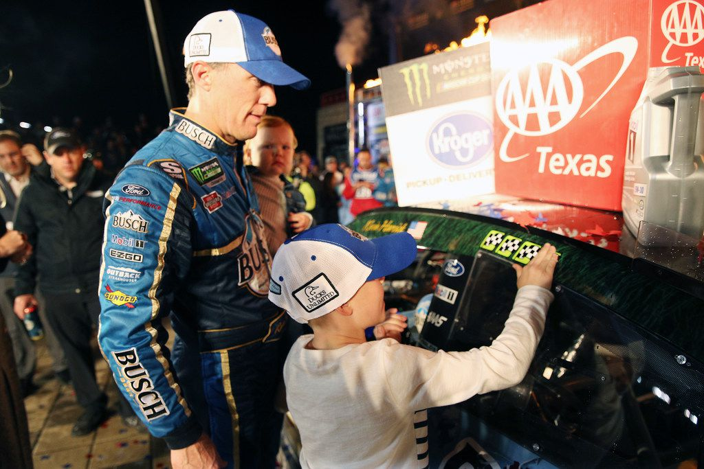 FORT WORTH, TEXAS - NOVEMBER 03: Kevin Harvick, driver of the #4 Busch Beer/Ducks Unlimited Ford, looks on as his son, Keelan, affixes the winners decal to his car in Victory Lane after winning the Monster Energy NASCAR Cup Series AAA Texas 500 at Texas Motor Speedway on November 03, 2019 in Fort Worth, Texas.