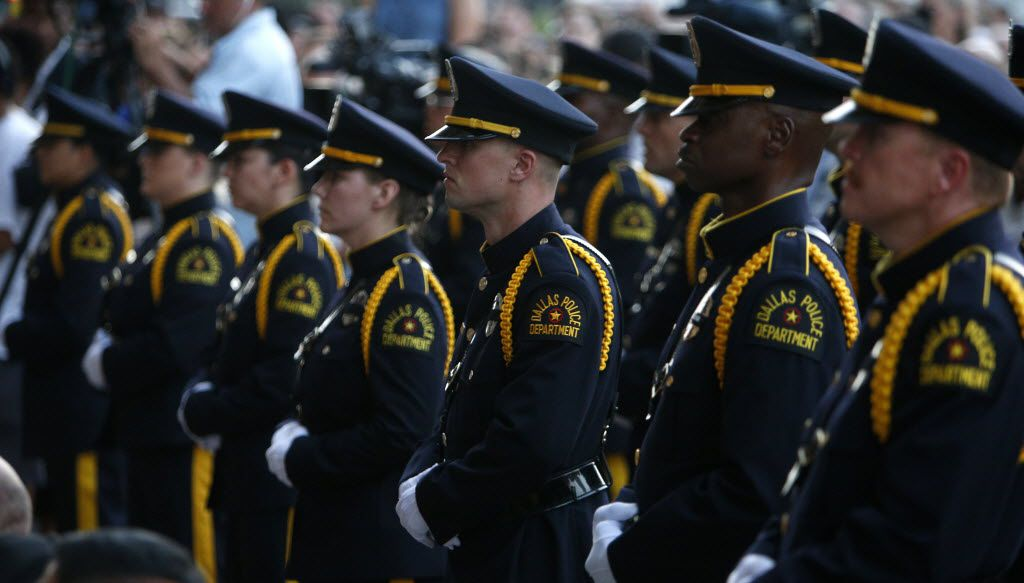 Dallas police officers stood at attention during a candlelight vigil hosted by the Dallas Police Association at Dallas City Hall on Monday.