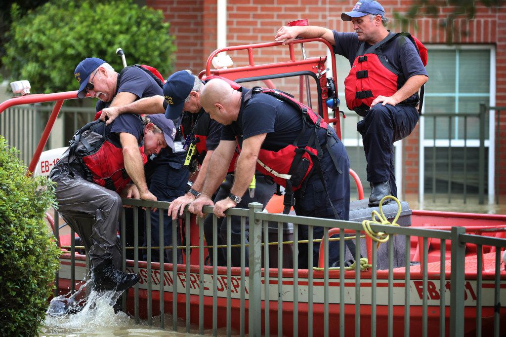 Donnie McComb is helped by fellow firefighters back onto their boat after he knocked on a door to follow up on a missing persons report in a flooded neighborhood of The Woodlands, north of Houston, Aug. 30, 2017. Waters began to recede in parts of flood-ravaged Houston on Wednesday as Tropical Storm HarveyÕs wrath shifted east. (Barbara Davidson/The New York Times)