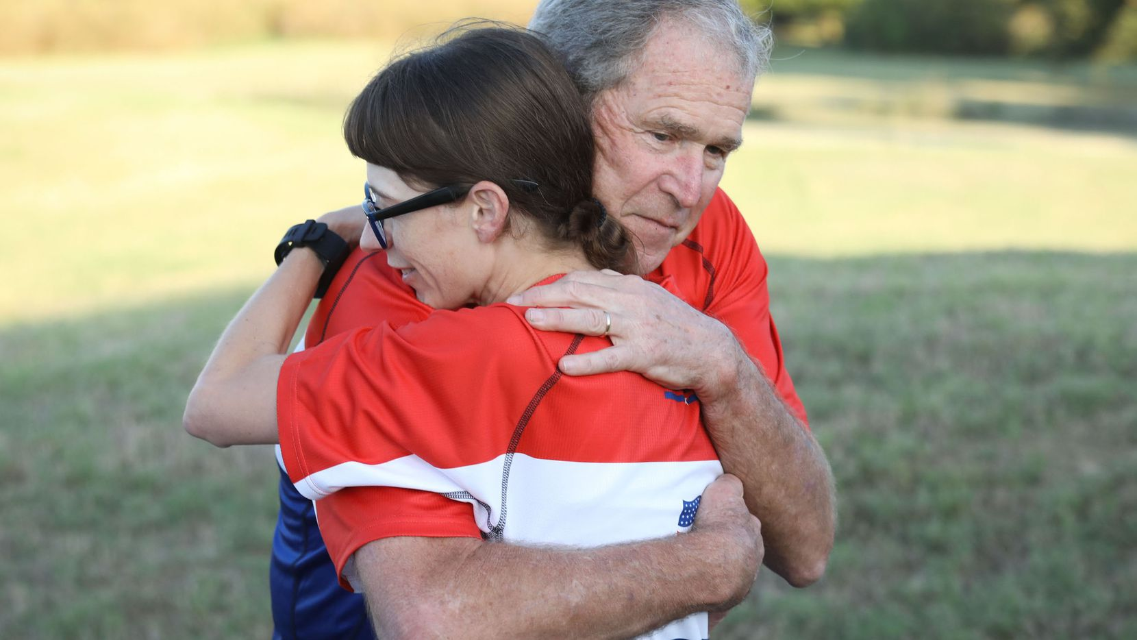 Former Pres. George W. Bush greets a participant in the Warrior 100K.