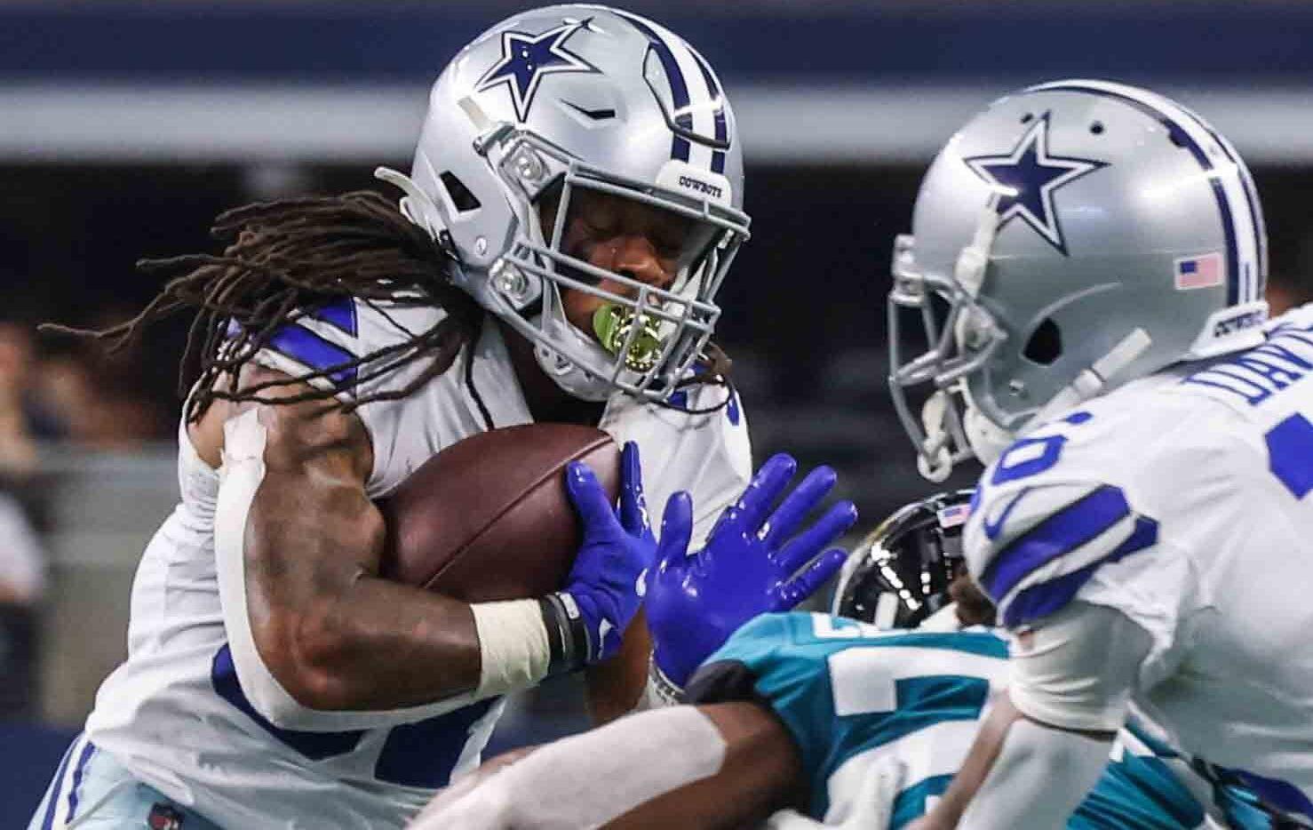 El corredor de los Cowboys de Dallas, JaQuan Hardy (der), protege el balón en un acarreo ante los Jaguars de Jacksonville en el juego de pretemporada efectuado en el AT&T Stadium de Arlington, el 29 de agosto de 2021.