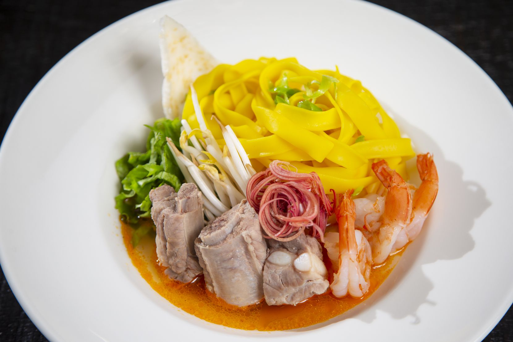Mì Quảng is made with shrimp, pork ribs, turmeric rice noodles and served in a tomato broth with lettuce, banana blossom and bean sprouts.