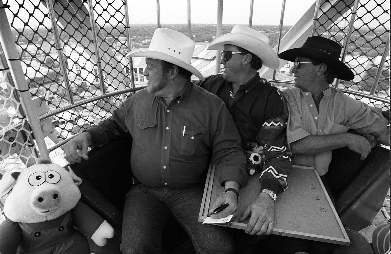 From left, Bo Fleming, Roger  Brooks, and Woody Killebrew, all from Garland, take a peek down on  the Midway at the State Fair of Texas from the top of the Texas Giant Ferris wheel. They took the stuffed animals they won along  for the ride. First day of the State Fair, Sept 30, 1994.