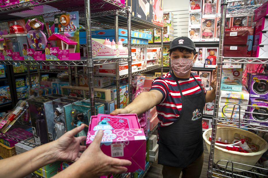 Manager Alec Contreras restocks supplies at The Toy Maven, which moved back into its repaired store this month, a year after tornadoes damaged the store.
