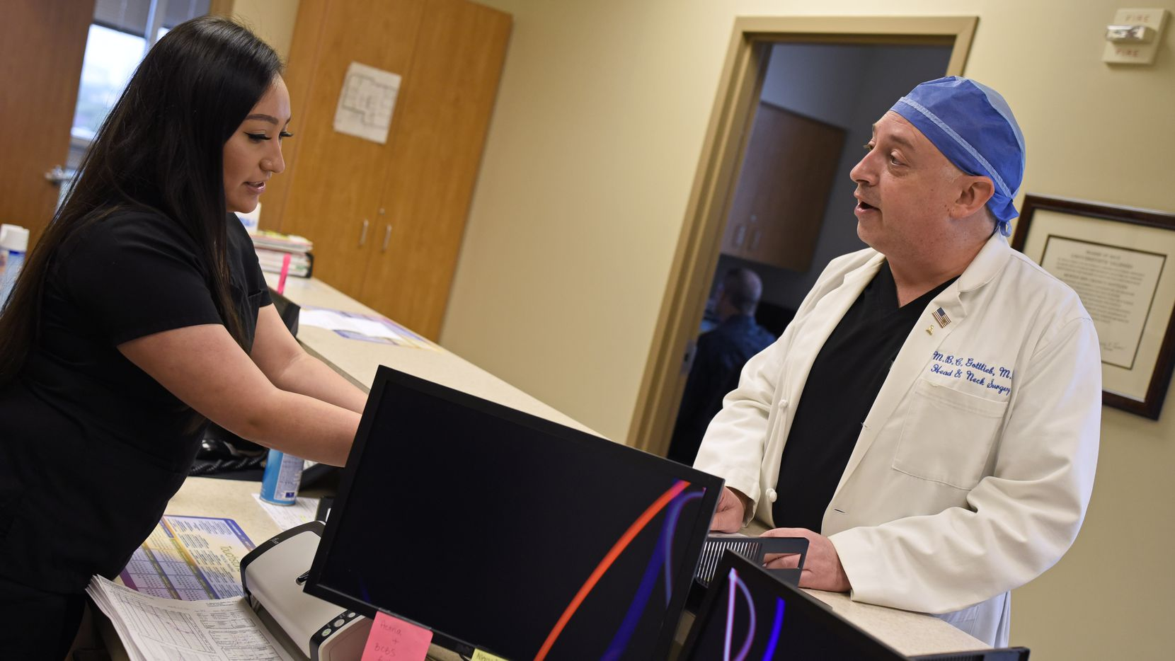 Medical assistant Ana Aguilar, left, speaks with Dr. Morris Gottlieb of North Dallas Ear, Nose & Throat in Richardson. Gottlieb is welcoming back patients after Texas loosened elective surgery rules, and he's adopted several additional safety procedures.