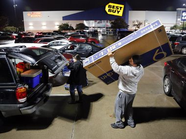 Thanksgiving Day shopper Jose Bazaldua of Dallas loads a 65-inch flat screen television into his SUV after taking advantage of a sale. Texas residents saved more than most from the 2017 tax cuts, which added to an already booming economy, according to a recent study.