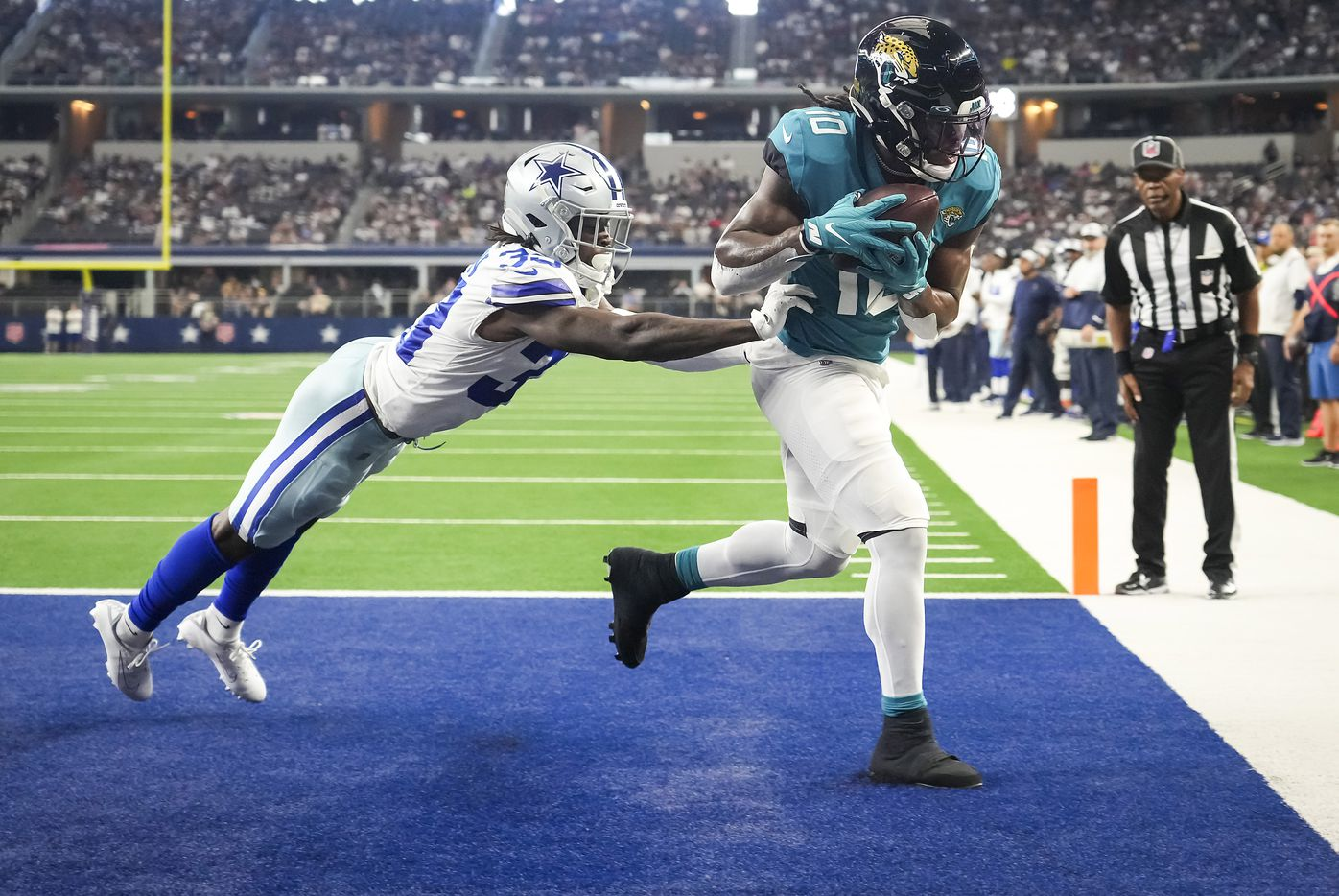 Jacksonville Jaguars wide receiver Laviska Shenault Jr. (10) hauls in a touchdown  pass as Dallas Cowboys defensive back Deante Burton (33) defends during the first half of a preseason NFL football game at AT&T Stadium on Sunday, Aug. 29, 2021, in Arlington. (Smiley N. Pool/The Dallas Morning News)