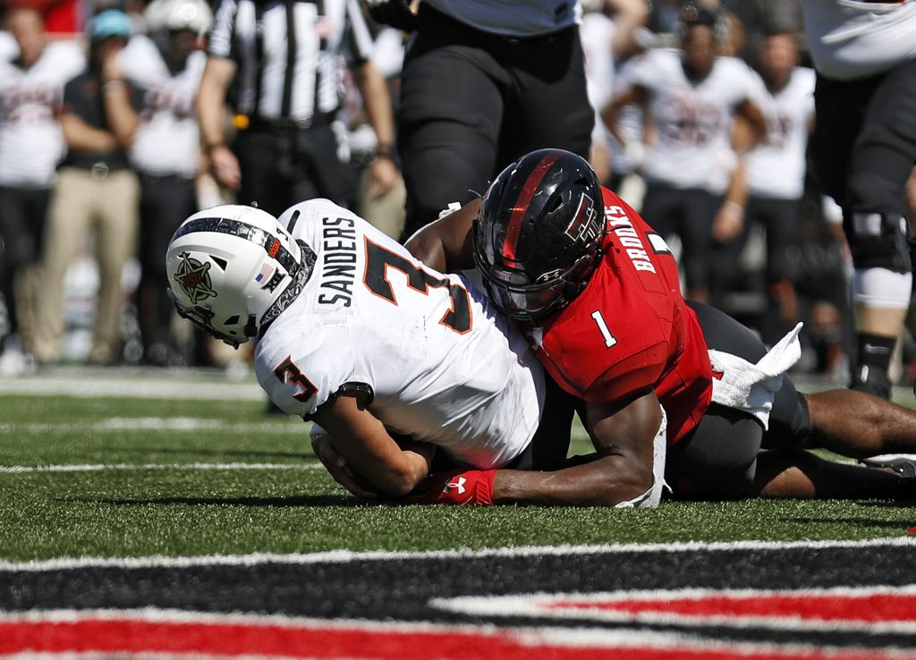 FILE - In this Oct. 5, 2019, file photo, Texas Tech's Jordyn Brooks (1) tackles Oklahoma State's Spencer Sanders (3) to stop a two-point conversion during the second half of an NCAA college football game, in Lubbock, Texas. Brooks was selected to The Associated Press All-Big 12 Conference team, Friday, Dec. 13, 2019. (AP Photo/Brad Tollefson, File)