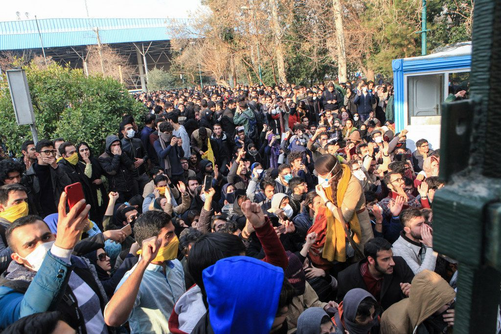 In this photo taken by an individual not employed by the Associated Press and obtained by the AP outside Iran, university students attend a protest inside Tehran University while anti-riot Iranian police prevent them to join other protestors, in Tehran, Iran, Saturday, Dec. 30, 2017.