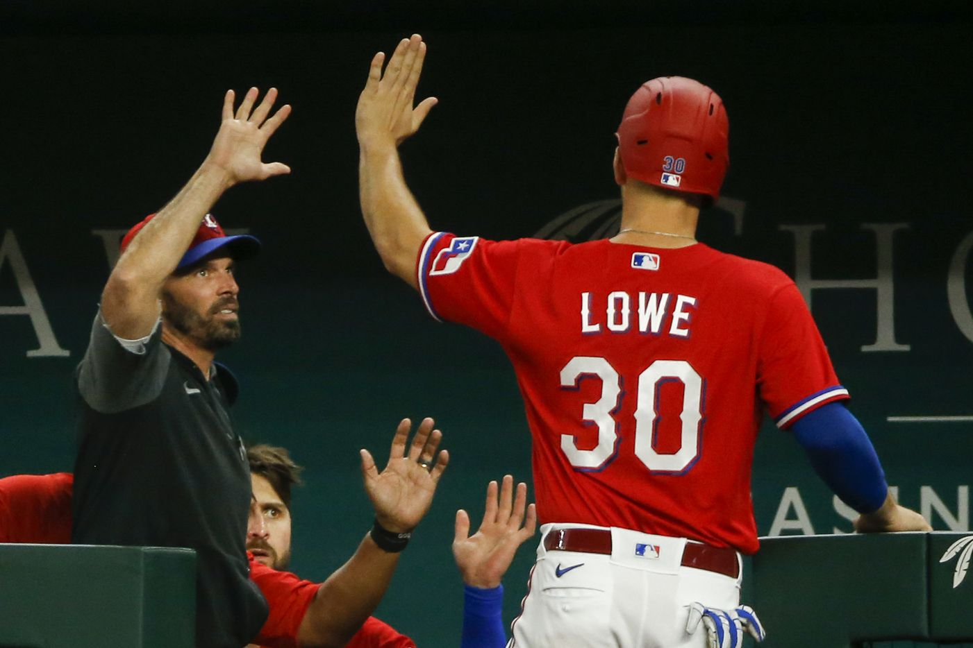 Texas Rangers first baseman Nate Lowe (30) high-fives Texas Rangers manager Chris Woodward (8) after scoring a run during the fourth inning against the Kansas City Royals at Globe Life Field on Friday, June 25, 2021, in Arlington. (Elias Valverde II/The Dallas Morning News)