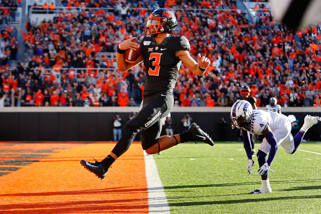 STILLWATER, OK - NOVEMBER 2:  Quarterback Spencer Sanders #3 of the Oklahoma State Cowboys leaps into the end zone for a 43-yard touchdown against safety Keenan Reed #4 of the TCU Horned Frogs only to have it called back for an illegal shift in the fourth quarter on November 2, 2019 at Boone Pickens Stadium in Stillwater, Oklahoma.  OSU won 34-27.