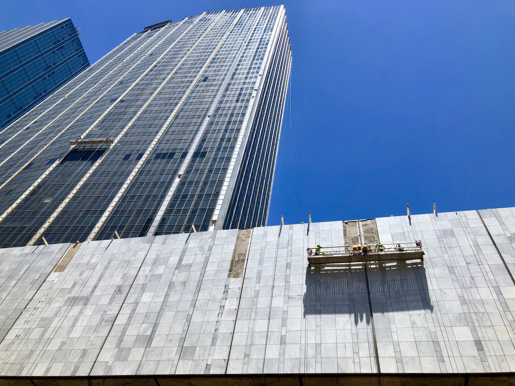 Construction workers are reinstalling the marble on the First National Bank buildings in downtown Dallas