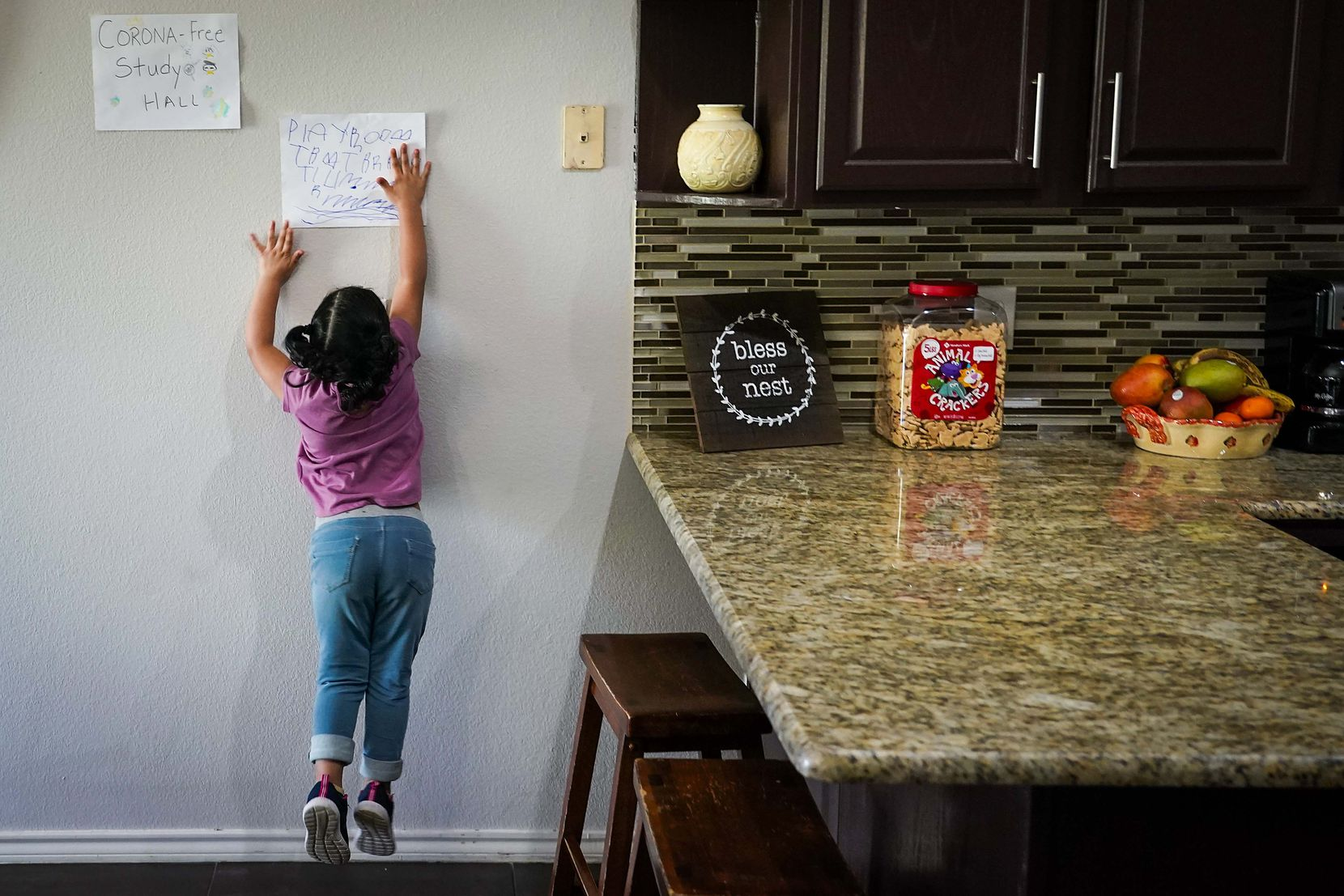 """Kamila Cabrera, 4, jumped to touch a sign in the kitchen of her family's Grand Prairie home labeling it a """"play room,"""" next to one for a """"corona-free study hall"""" after distance learning began in March. North Texas families had to adopt new school routines when the pandemic hit."""