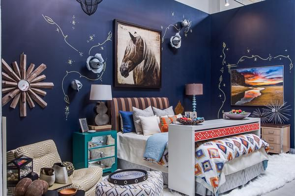 Pickard Design Studio Sarah Pickard used a moody navy in her bedroom vignette. Handpainted gold flourishes and rosettes that add luxury to a space layered with turquoise, orange, blues and browns.