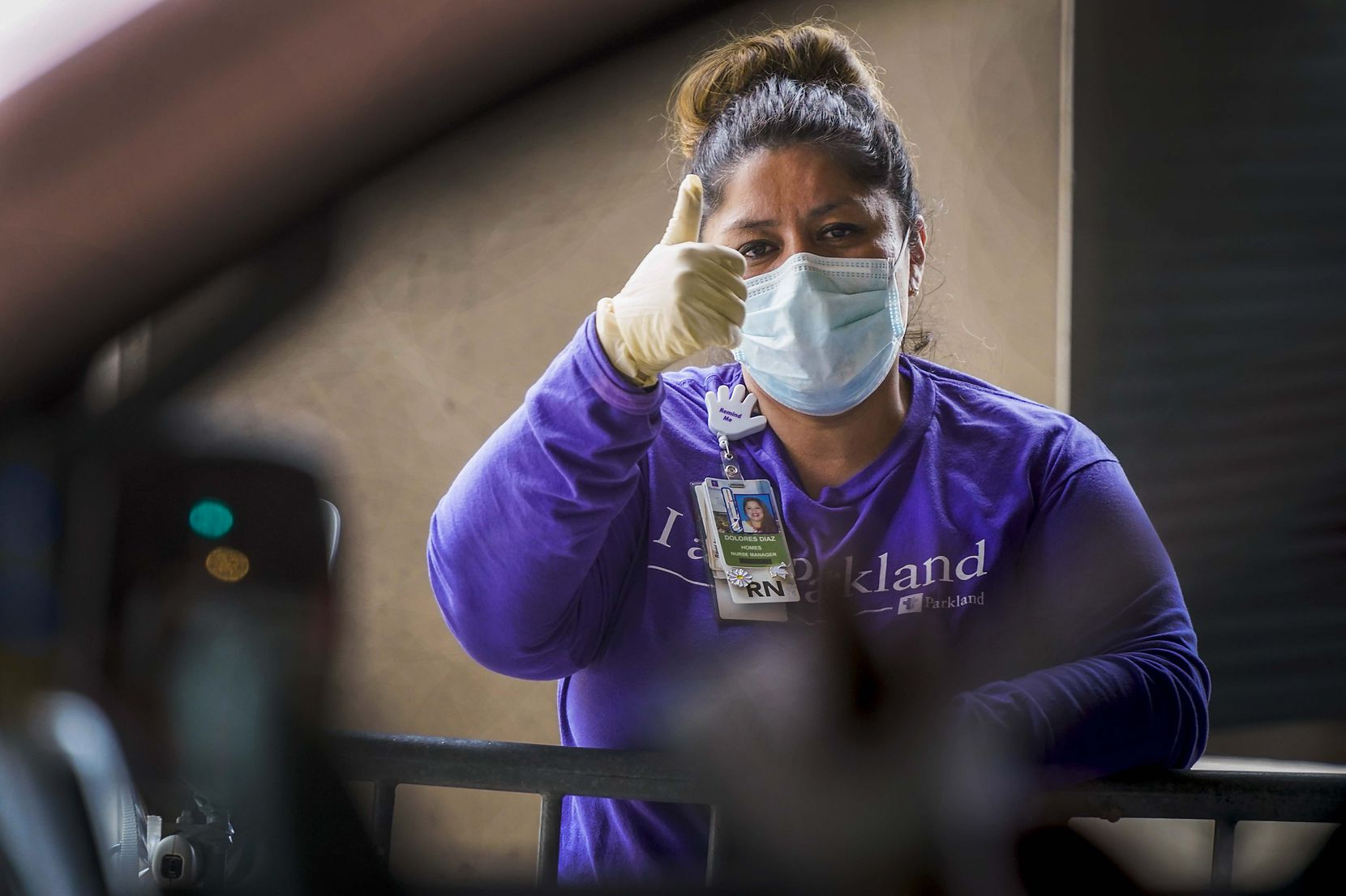 Dolores Diaz, Parkland Homeless Outreach Medical Services (HOMES) program nurse manager, gives a thumbs up to a patient at a COVID-19 drive-through testing site at American Airlines Center on April 20, 2020.