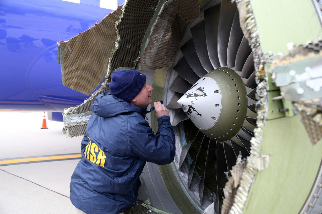 In this National Transportation Safety Board photo, NTSB investigator Jean-pierre Scarfo examines damage to the CFM International 56-7B turbofan engine belonging Southwest Airlines Flight 1380 that separated during flight. Investigators can't explain with certainty why the left engine in the Boeing 737 malfunctioned but are directing their attention to metal fatigue on fan blades. (Keith Holloway/National Transportation Safety Board via Getty Images)