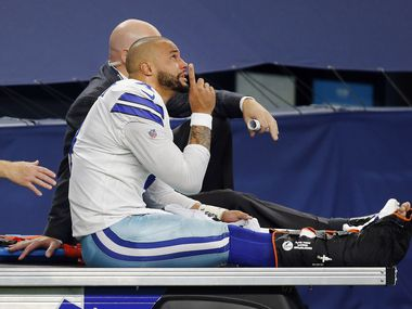 With tears in his eyes, Dallas Cowboys quarterback Dak Prescott (4) points skyward as he is carted off the field after sustaining a leg injury in the third quarter at AT&T Stadium Stadium in Arlington, Texas, Sunday, October 11, 2020. The Cowboys are facing the New York Giants.