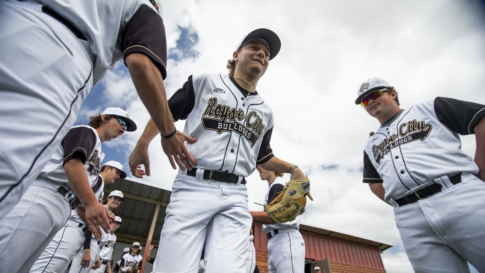 Gavin Lynch, 18, slaps hands with his teammates during player introductions before a high school baseball game at Royse City High School, Saturday, April 24, 2021. Lynch broke through has a key player for the baseball team last year as a junior, but COVID-19 ended the season early. It turns out it would be his last baseball season. For the majority of his life, Gavin has had a kidney condition that he and his family knew would ultimately lead to kidney failure. They just didn't know when. It happened this year. He's been going to dialysis 3-4 times a week for months and the only thing that could fix that is a new kidney.