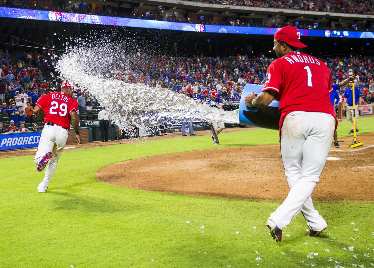 Texas Rangers third baseman Adrian Beltre (29) runs away from a Gatorade dump by shortstop Elvis Andrus (1) after a 7-3 win over the Seattle Mariners on Friday, June 3, 2016 at Globe Life Park in Arlington, Texas.  (Ashley Landis/The Dallas Morning News)