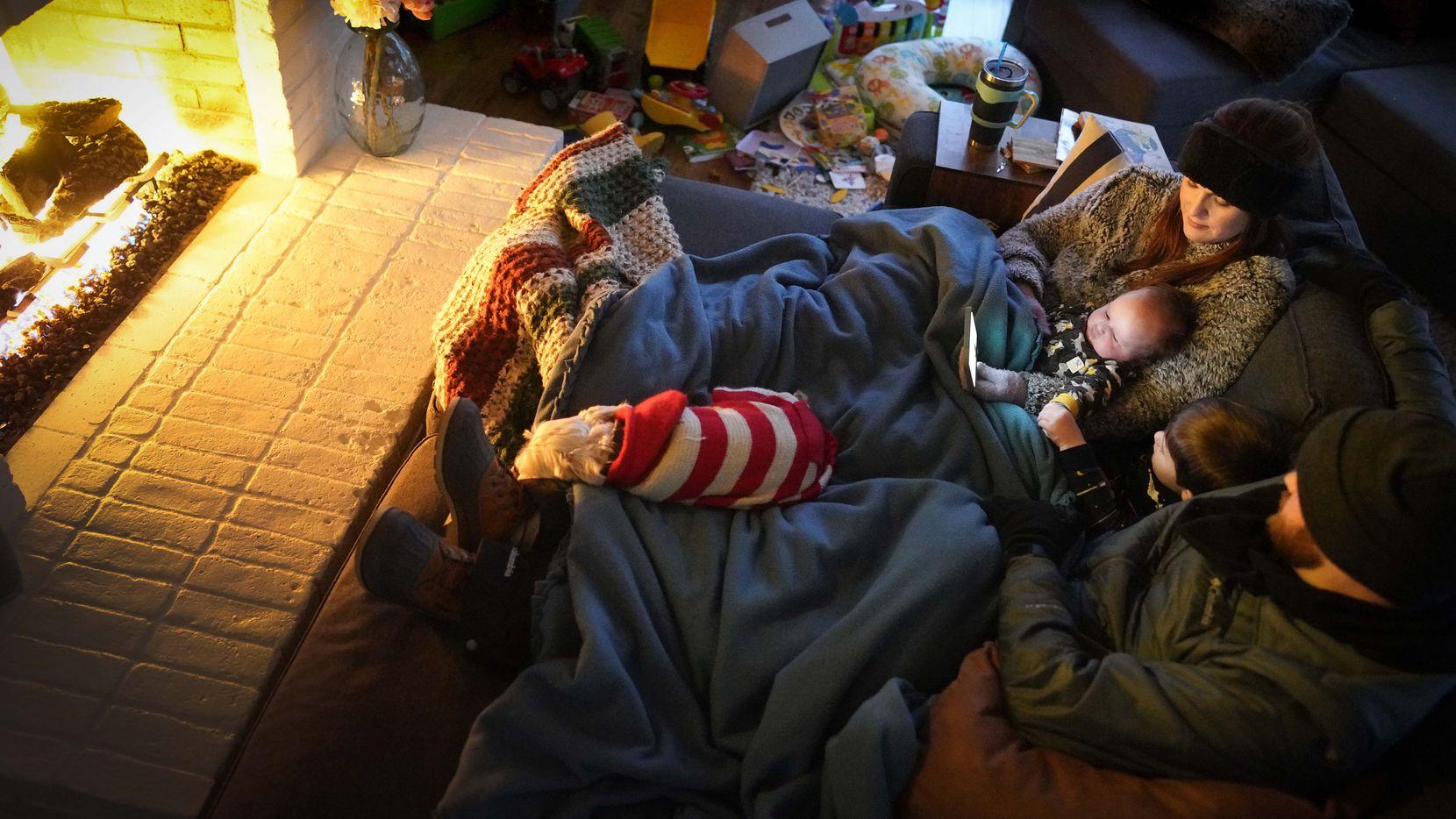 Dan Bryant y su esposa Anna se abrazan ante la chimenea junto a sus hijos Benny, de 3 años, y Sam, de 12 semana. Los Bryant fueron una de cientos de miles de familia que se quedaron sin luz durante la nevada del domingo. ERCOT no ha podido reestablecer el servicio a casi un millón de familias.