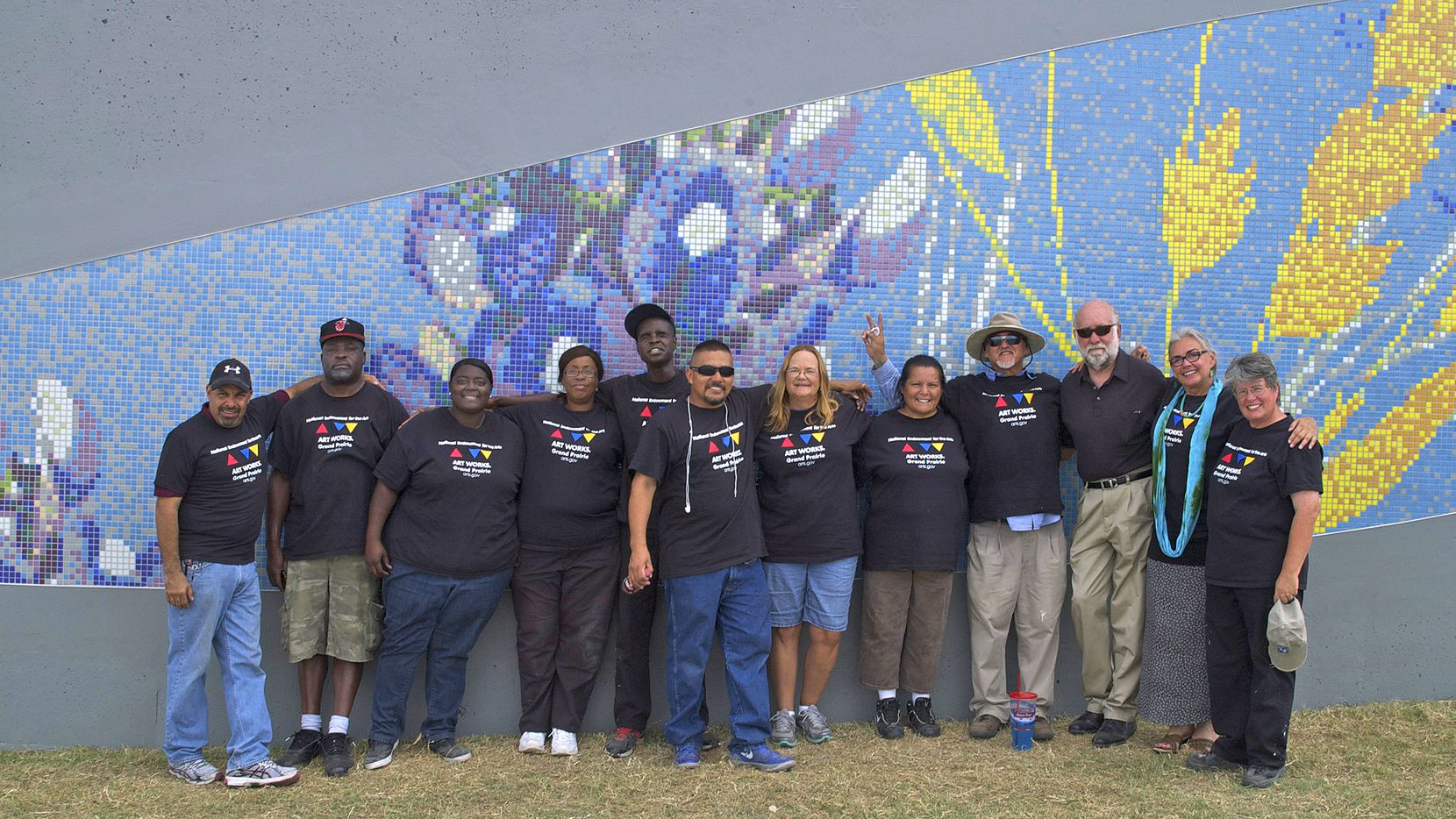 A group of ex-offenders and city of Grand Prairie staffers and volunteers pose in front of part of a mosaic tile illustration along a stretch of Interstate 30.