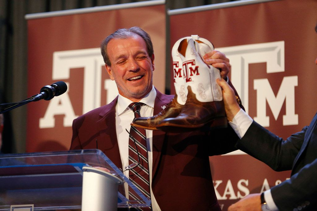 Texas A&M's new coach Jimbo Fisher receives a pair of new boots during a press conference at Kyle Field in College Station, Texas on Dec. 4, 2017.  (Nathan Hunsinger/The Dallas Morning News)