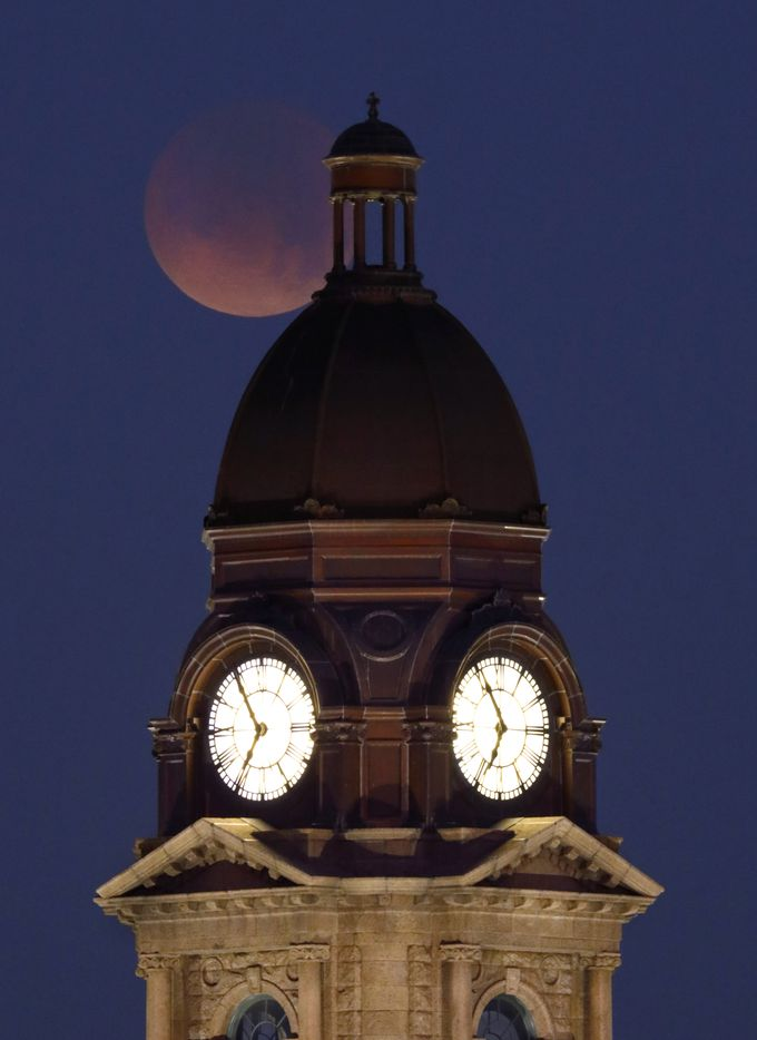 A partial Super Blue Blood Moon begins to set over the old Tarrant County Courthouse in downtown Fort Worth on Jan. 31, 2018. The rare lunar eclipse last happened in 1866.