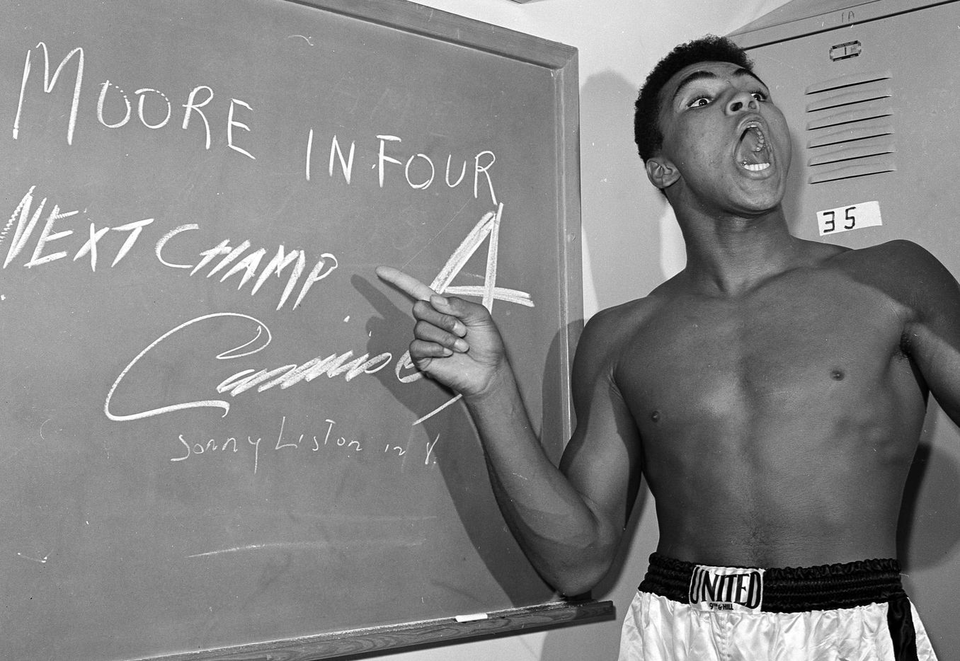FILE - In this Nov. 15, 1962, file photo, young heavyweight boxer Cassius Clay, who later changed his name to Muhammad Ali,  points to a sign he wrote on a chalk board in his dressing room before his fight against Archie Moore in Los Angeles, predicting he'd knock Moore out in the fourth round, which he went on to do.  The sign also predicts Clay will be the next champ via a knockout over Sonny Liston in eight rounds. He did it in seven rounds.