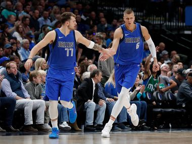 Dallas Mavericks' Luka Doncic (77) and Kristaps Porzingis (6) celebrate a basket by Porzingis in the second half of an NBA basketball game against the Portland Trail Blazers in Dallas, Sunday, Oct. 27, 2019. (AP Photo/Tony Gutierrez)