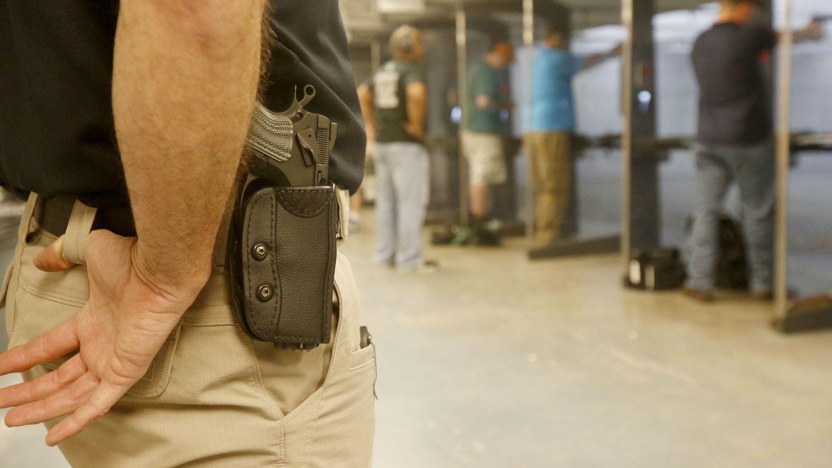 Shooting instructor Mark Brushwiller wears his gun on his hip at the Frisco Gun Club.