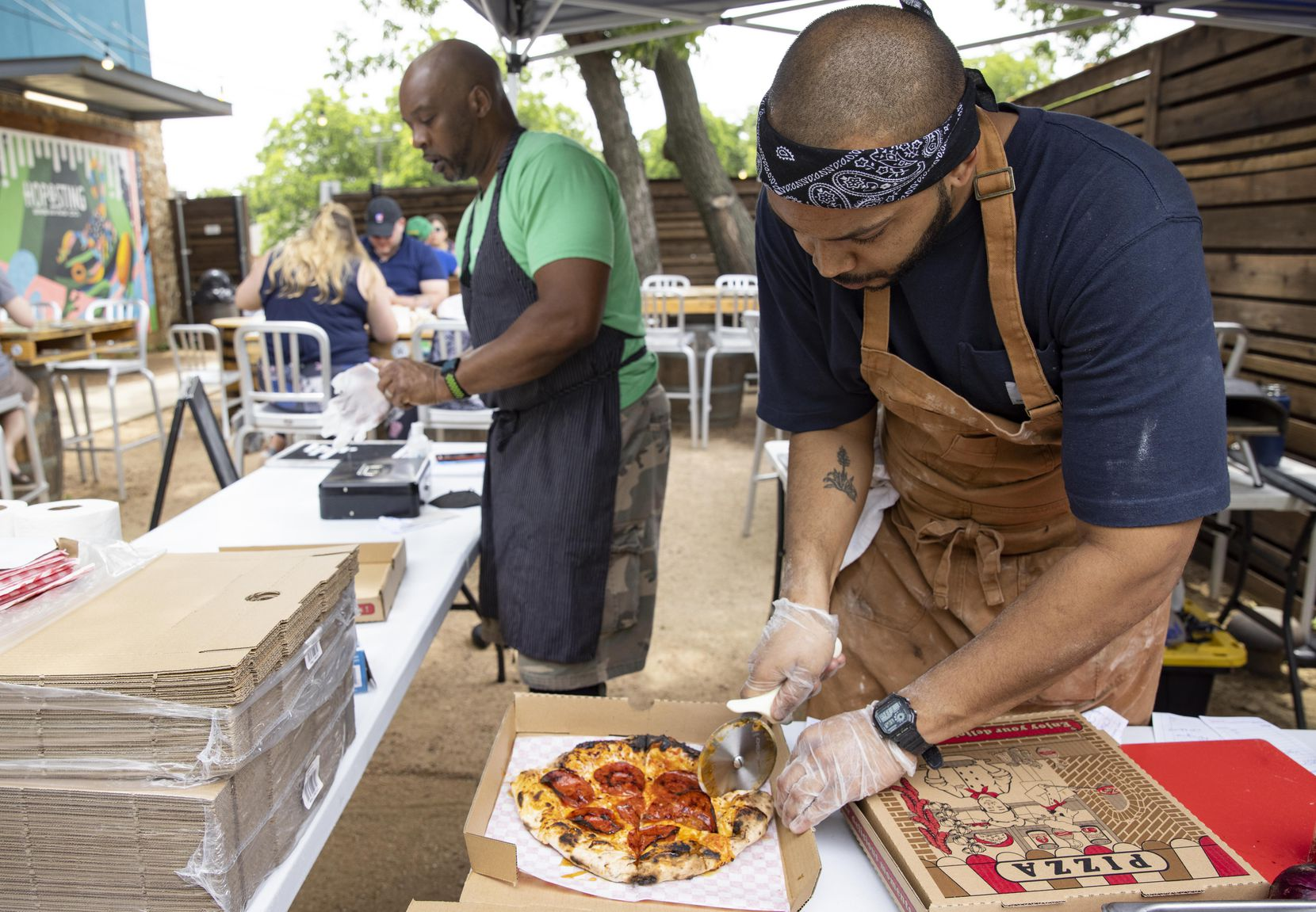 Desmon Coleman, owner of Hustle Town Pizza, boxes up a spicy pepperoni pizza while dad James Coleman takes orders at Hop and Sting Brewing Co. in Grapevine.