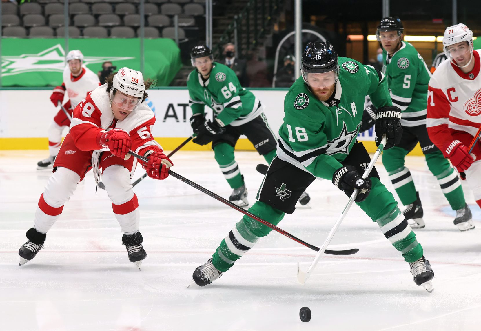 Dallas Stars center Joe Pavelski (16) secures the puck as Detroit Red Wings left wing Tyler Bertuzzi (59) reaches during the second period of play at American Airlines Center on Tuesday, January 26, 2021in Dallas. (Vernon Bryant/The Dallas Morning News)