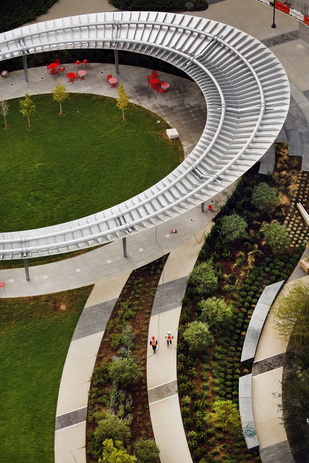 An overhead view of Pacific Plaza shows The Pavilion, a floating 95-by-138-foot ovoid structure of stainless steel. Perforated Morse Code signatures of every railroad stop along the Texas and Pacific Railroad between El Paso and New Orleans punctuate the steel ring. Pacific Plaza, a new Dallas park project along Harwood and St. Paul Streets, will add another green space in downtown, Wednesday, October 9, 2019. (Tom Fox/The Dallas Morning News) Surrounded by high-rise buildings, Pacific Plaza, Dallas' newest downtown park, was designed by landscape architects SWA Group, with a signature pavilion designed by HKS Laboratory for Intensive Exploration (LINE). The land was acquired in 2008 by the City of Dallas with the support of Trust for Public Land. The design and construction of the Pacific Plaza park itself was spearheaded by Parks for Downtown Dallas in a public/private partnership with the City of Dallas.