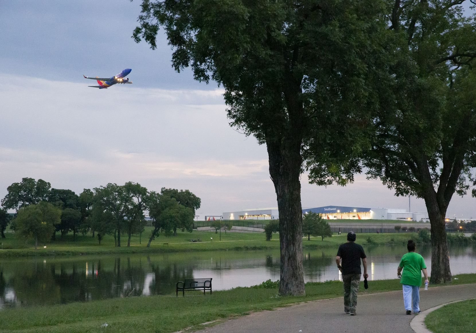People walk on the northern side of Bachman Lake Park. Among the five options short-listed from a group of 11 for an alternate entry to Dallas Love Field, three would have a major impact on the park.