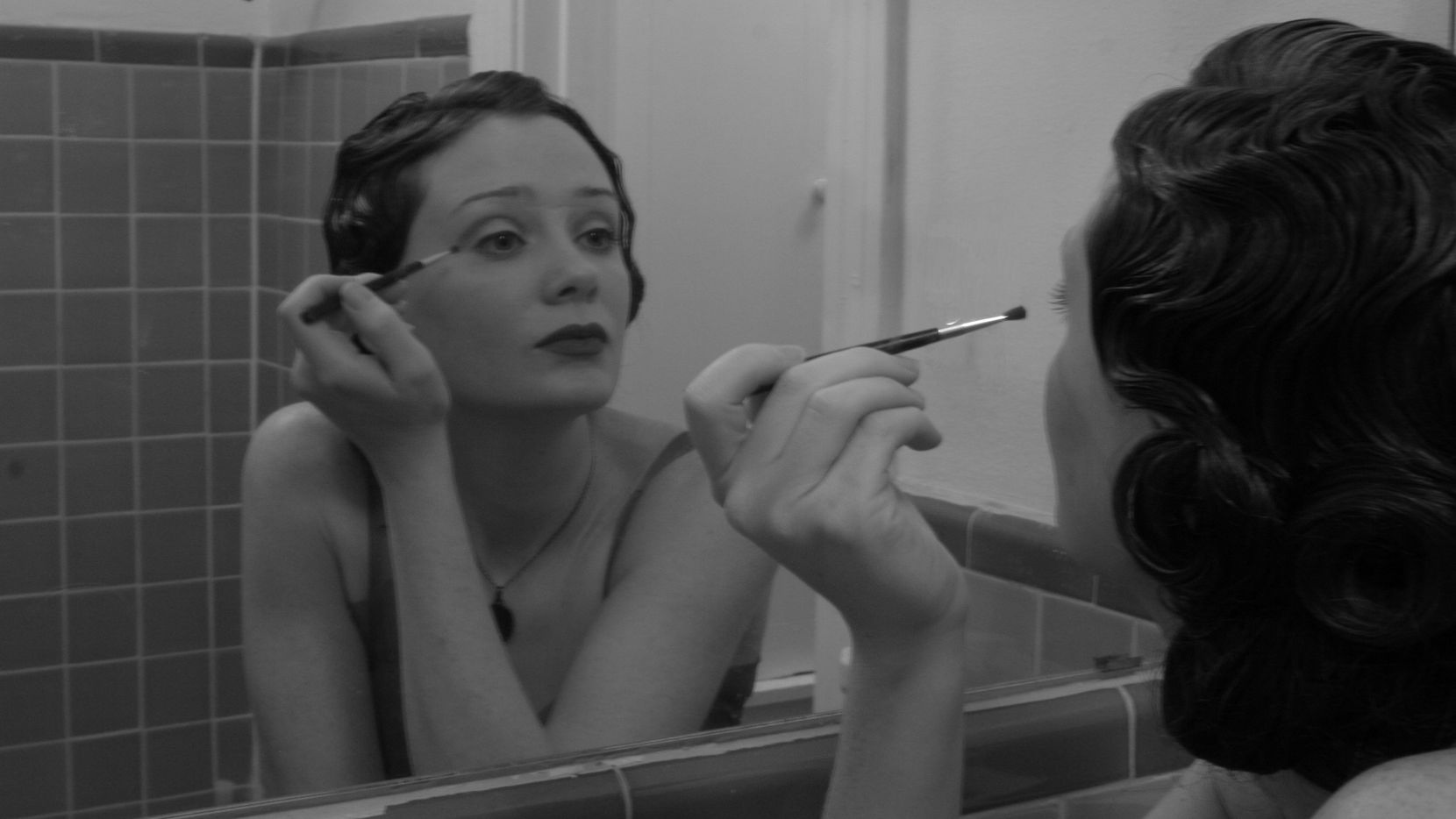 Singer-songwriter Kristy Kruger looks into the mirror while putting on makeup.