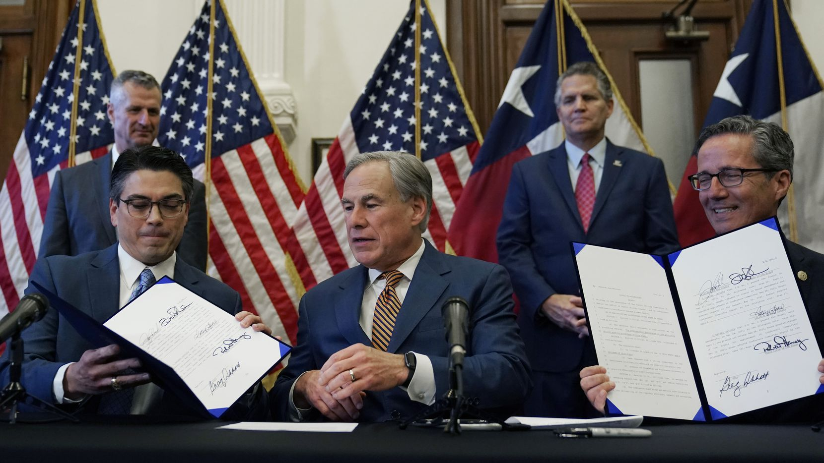 With the help of Marshall GOP state Rep. Chris Paddie, left, and North Richland Hills GOP state Sen. Kelly Hancock, right, Gov. Greg Abbott, center, displays two electricity grid bills he signed Tuesday. The bills overhaul the Electric Reliability Council of Texas (ERCOT) and weatherize and improve the reliability of the state's power grid.