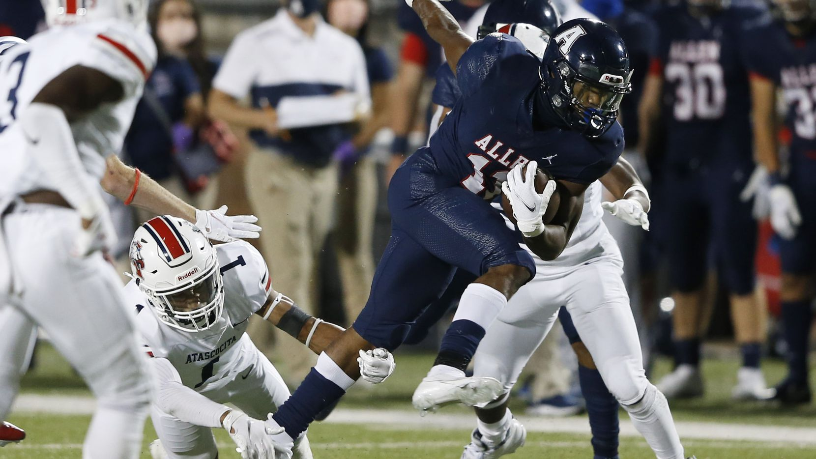 Allen's Jordan Johnson (11) is tripped up by Humble Atascocita's Jordan Augustine (1) on a play during the first quarter at Eagle Stadium in Allen, Texas on Friday, October 2, 2020. (Vernon Bryant/The Dallas Morning News)