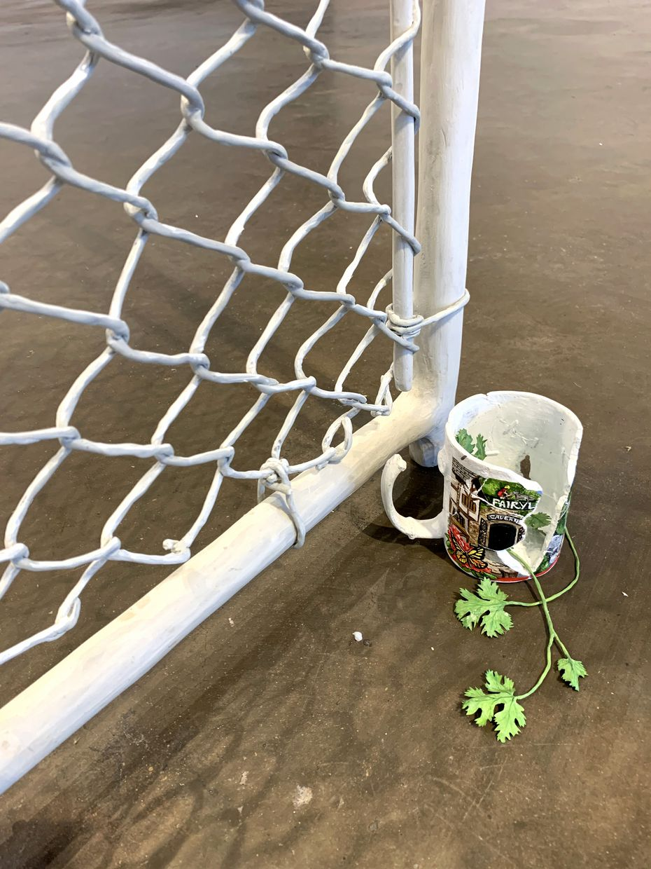 "Installation detail that includes three pieces: 'Rock City mug,' 2020, bronze, oil-based paint; 'Gate with cherries,' 2020, PVC pipe, rope, resin, woven aluminum wire, pigmented resin, epoxy puttying and 'Cilantro bouquet,' 2020, Tyvek, wire, epoxy putty, acrylic paint at the exhibition ""How to fold a fitted sheet"" at Ex Ovo gallery through Nov. 1, 2020."