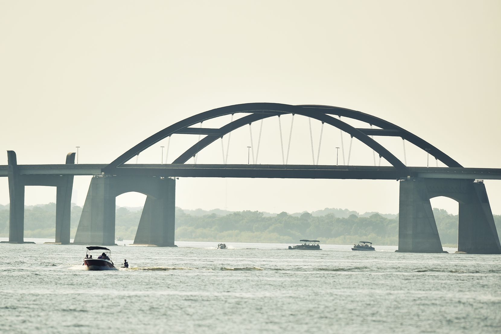 Boaters enjoy the warm sunny weather on Lewisville Lake near the Lewisville Lake toll bridge.