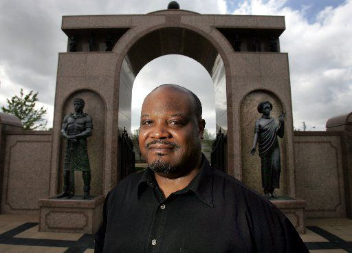 ORG XMIT: *S0416023529* Artist David Newton, of Dallas, poses in front of the archway entrance of the Freedman's Cemetery (which he designed) in Dallas on Wednesday, March 29, 2006. He has also been commissioned to design the art element at Memorial Park's Veteran Memorial in Plano. 04122006xMETROcc