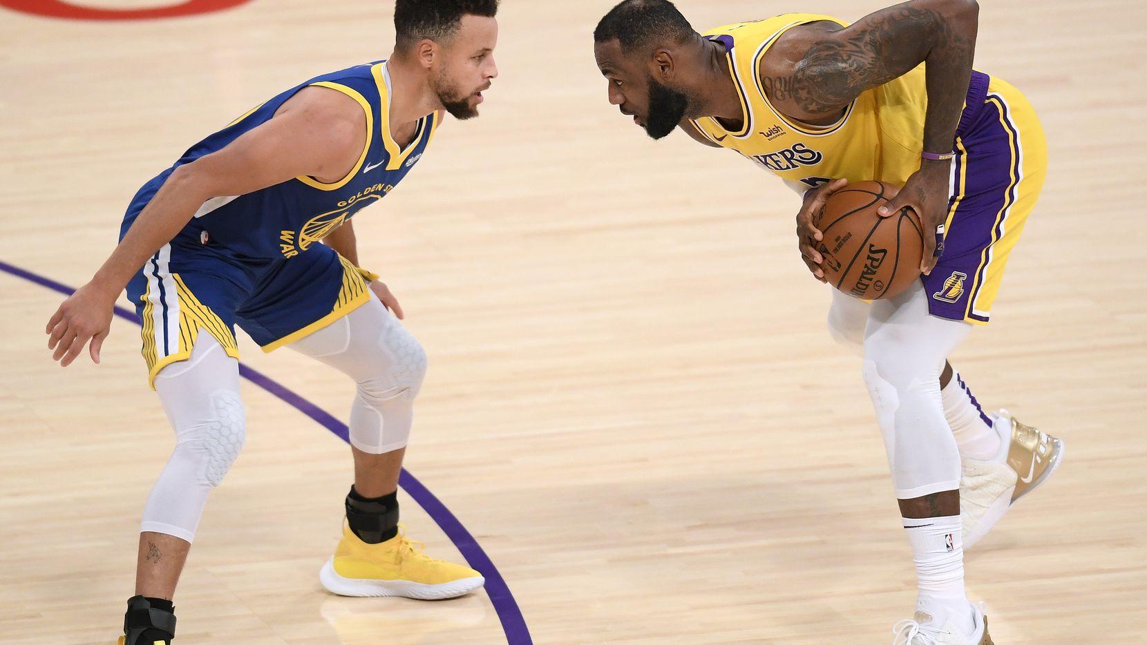 El estrella de los Lakers de Los Ángeles, LeBron James, es custodiado por el estelar de los Warriors de Golden State, Stephen Curry, el 18 de enero de 2021 en el Staples Center de Los Ángeles.