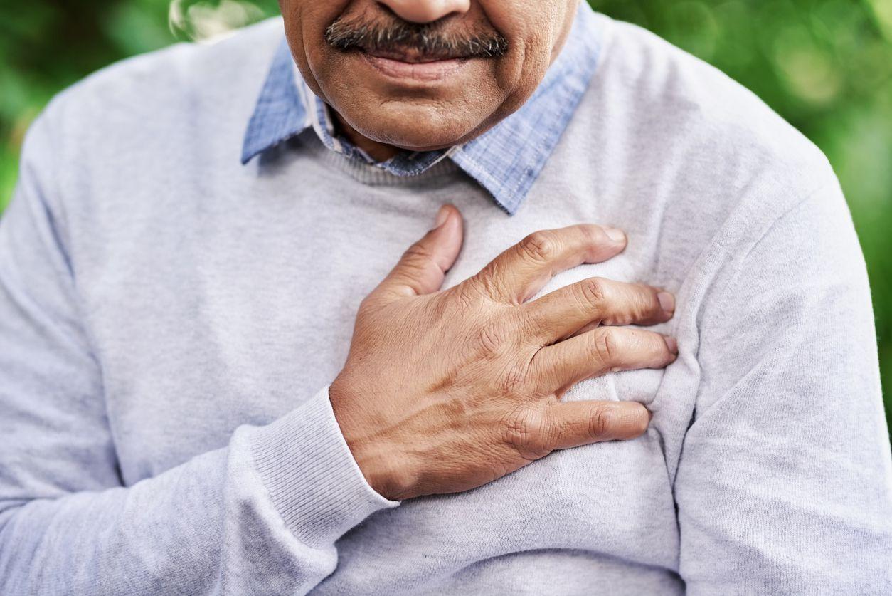 Un adulto se toca el pecho por dolor y síntoma de un ataque cardiaco.