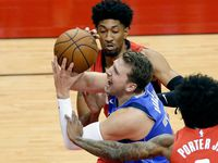 Dallas Mavericks guard Luka Doncic (77) is fouled as he drives to the basket between during the first half of an NBA basketball game Wednesday, April 7, 2021, in Houston.