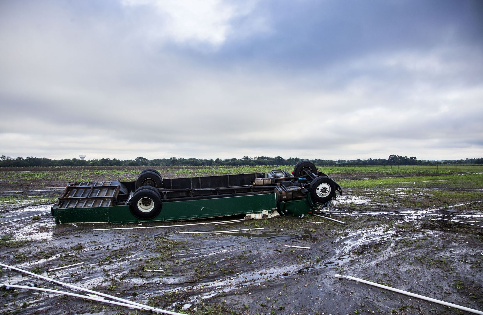 An overturned truck with Spirit of Waxahachie Indian Band written on the side sits in an empty field after a rainstorm at Waxahachie High School on Oct. 13.