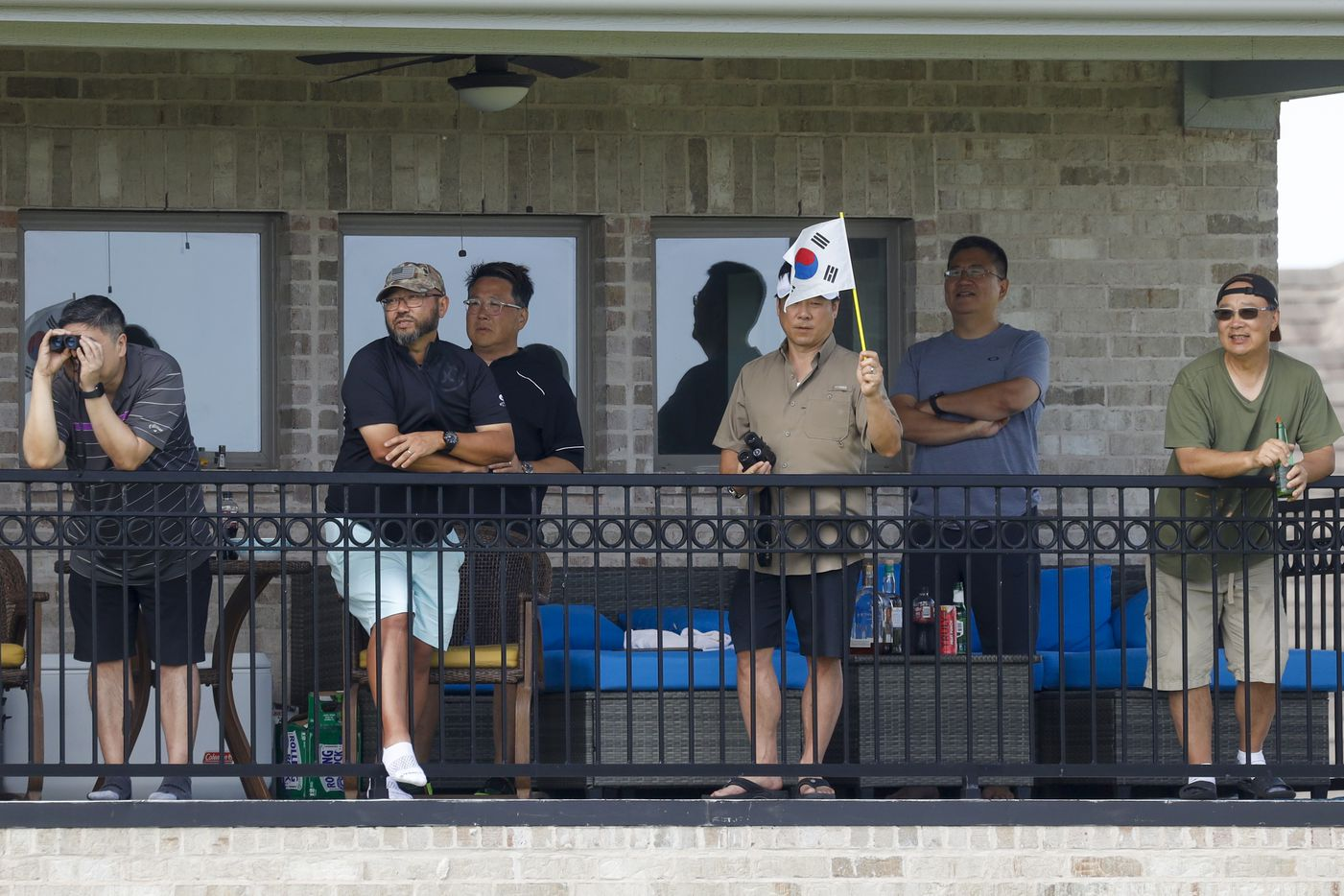 Fans watch action alongside the No. 2 green from a second floor balcony during the third round of the LPGA VOA Classic on Saturday, July 3, 2021, in The Colony, Texas. (Elias Valverde II/The Dallas Morning News)