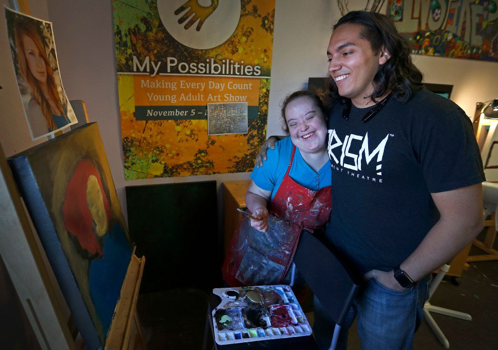 Jonah Gutierrez (right), theater teacher and technical director of PrismCo, hugs his student Rosie Alvarado, who  painted a portrait of actress Debbie Crawford during an art class.