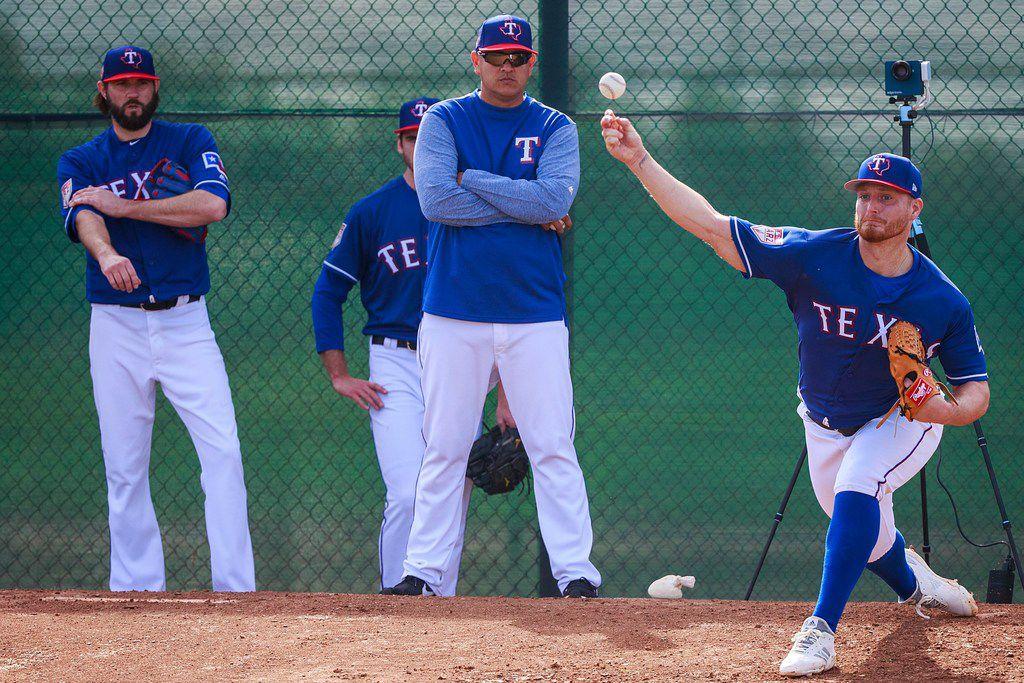 El coach de pitcheo de los Texas Rangers, Julio Rangel, observa con los brazos cruzados al lanzador Shelby Miller durante una práctica el 15 de febrero de 2019 en Arizona