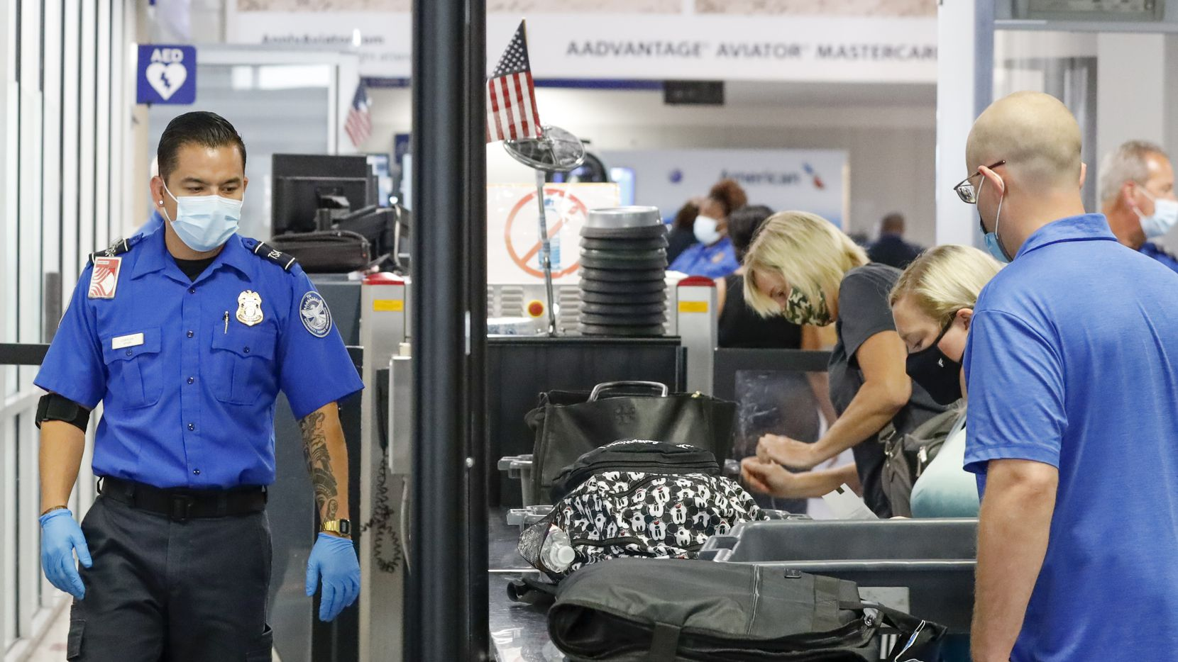 A Transportation Security Administration agent watches travelers place their belongings in containers at a security checkpoint at DFW International Airport on Sept. 2.